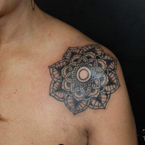 Fiore in stile geometrico sulla spalla
