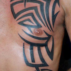 Tribale che si sviluppa dal petto lungo le costole